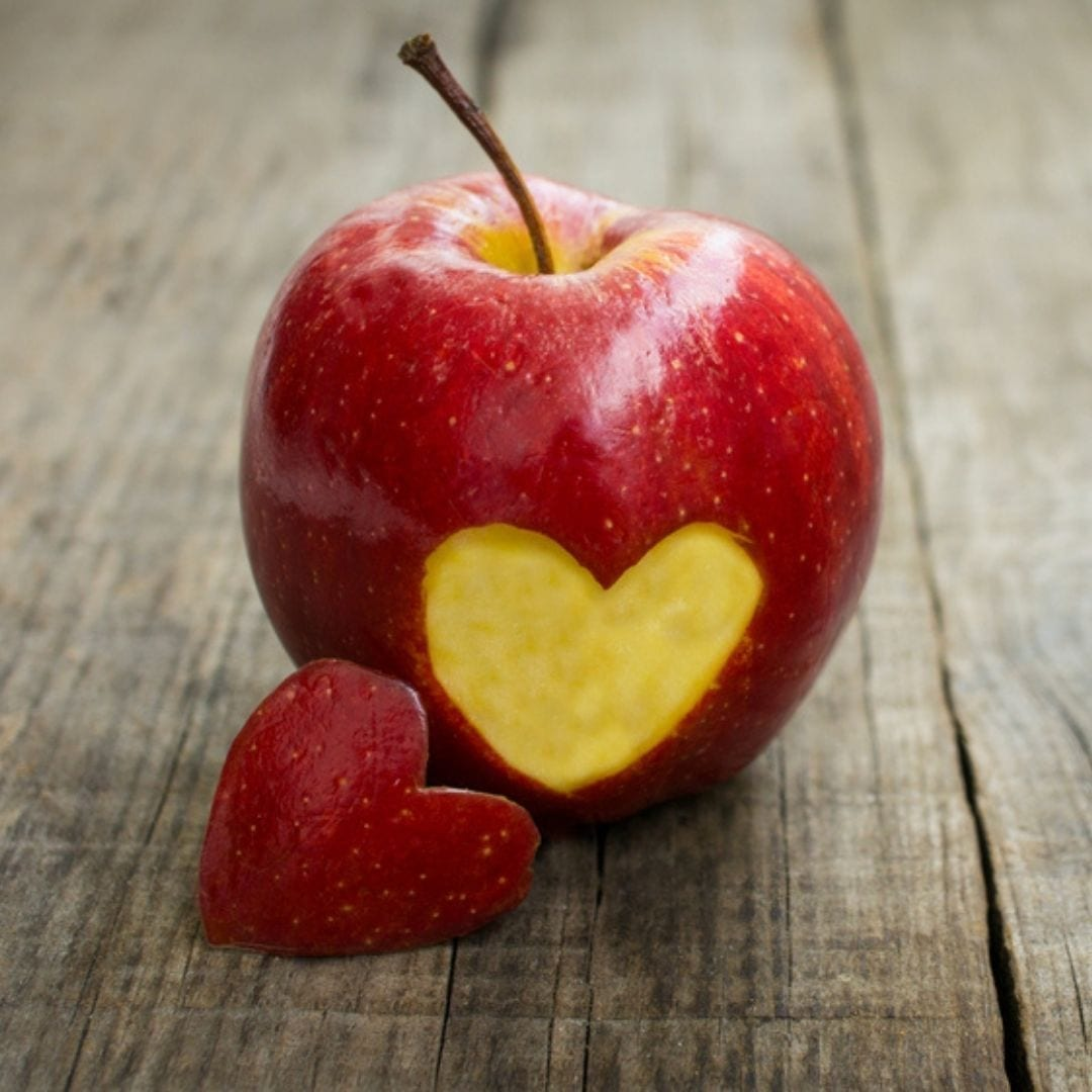 apple with a heart bitten into it